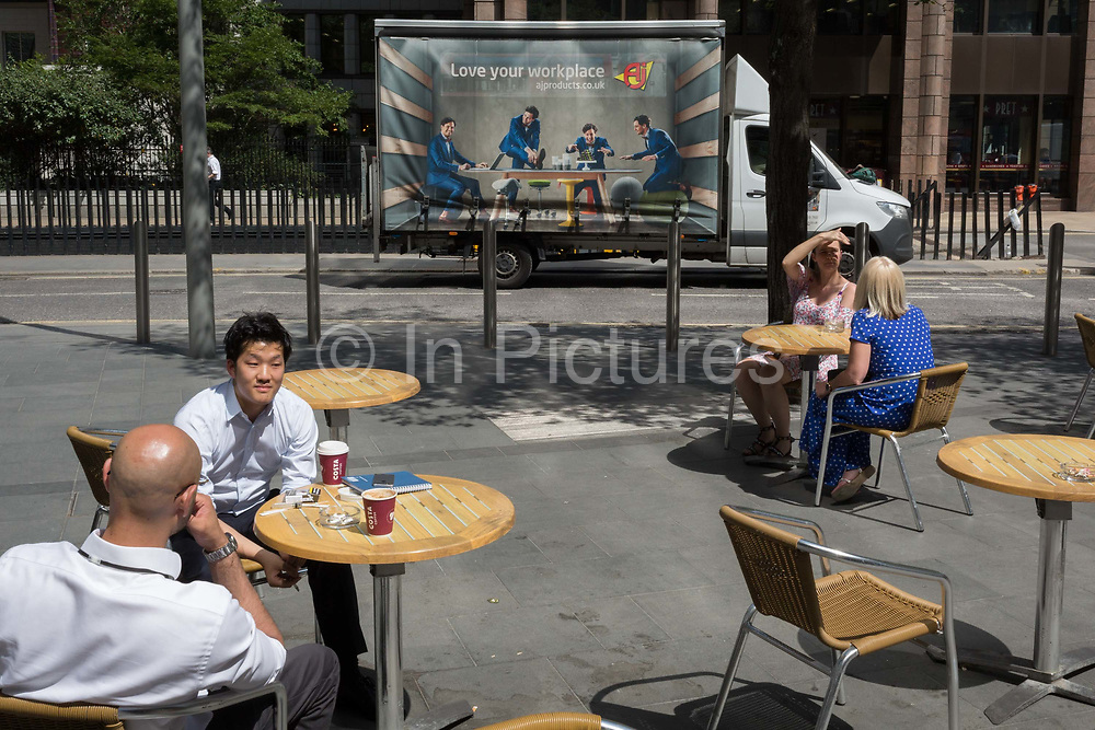 As heatwave temperatures climb to record levels - the hottest day of the year so far - Londoners in the City of London the capitals financial district aka the Square Mile enjoy sunshine on St. Mary Axe Street, on 25th July 2019, in London, England.