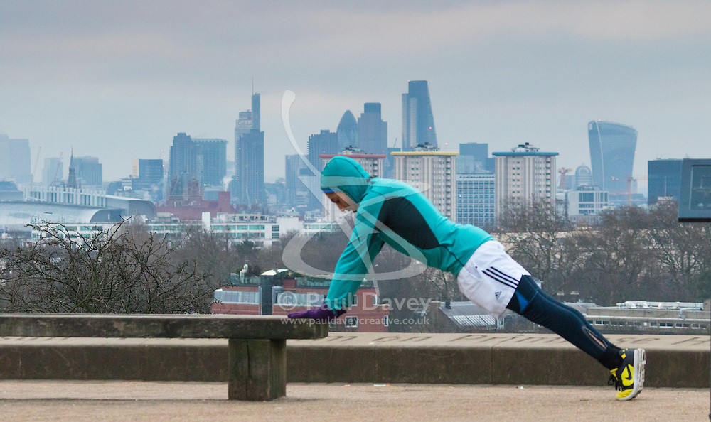 Primrose Hill, London, February 15th 2015. A man does push-ups with the skyline of the City providing a backdrop on a chilly early morning on Primrose Hill, overlooking London's skyline.<br /> ///FOR LICENCING CONTACT: paul@pauldaveycreative.co.uk TEL:+44 (0) 7966 016 296 or +44 (0) 20 8969 6875. ©2015 Paul R Davey. All rights reserved.