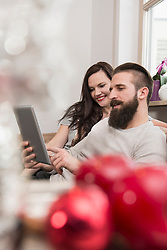 Couple watching digital tablet on sofa