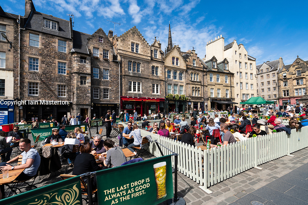 Many people drinking in bars outdoors in warm weather at Grassmarket in Edinburgh Old town, Scotland, UK