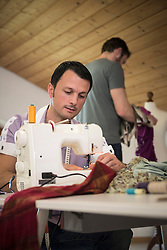 Male dressmaker stitching cloth on sewing machine with his colleague in background, Bavaria, Germany