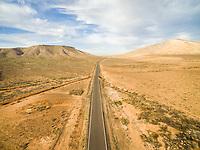 Aerial view of an empty road in dryland of Fuerteventura, Canary Islands.