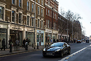 An expensive Aston Martin car drives down the King's Road, Chelsea, London, United Kingdom.  This street is part of a very affluent area of London and its famous for its rich residents and designer shops.