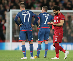 Liverpool's Mohamed Salah (right) adjusts a bandage on his wrist as Red Star Belgrade's Marko Gobeljic and Nenad Krsticic look on