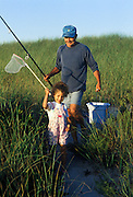 Grandfather walking along a dune path with granddaughter after fishing together. Cape Cod