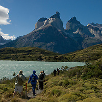 Hikers walk beside Lake Nordenskjold, below the Horns of Paine in Torres del Paine National Park, Chile.