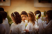 A boy surrounded by other children at their first communion in a Catholic Church in Orte Italy.
