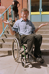 Male wheelchair user in front of steps protesting about lack of access,