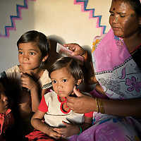 Ramvati Adivasi relaxes with her grandchildren in her home in the village of Patara, 20km from Shivpuri. Adivasi is from a tribal community (Scheduled Tribe) and works as a program maker at Dharkan 107.8. Before the official launch of the community radio station in July 2009, Adivasi and her colleagues have recorded several programs informing women of government health services. As well as her role at Dharkan 107.8, Adivasi is is an ASHA (local female health advisor). She provides a free referral service to local women, keeping them in touch with government health services. Adivasi receives a fee from the government for every referral. This is one means by which the government and partners UNICEF are increasing the rate of institutional deliveries in Madhya Pradesh state. ..Shivpuri district in Madhya Pradesh suffers from poor health outcomes. Of particular concern is the high rate of maternal mortality. One of the Indian government's aims, with partners Unicef, is to encourage the population to adopt practices to improve sanitation and health practices. In an area made up of traditionally disadvantage groups and suffering low literacy rates, this can be a challenge. ..A survey found that radio was the most readily accessible media by the Shivpuri community with more than half saying they tuned in several times a day. ..Dharkan 107.8 FM will go on air in July. The station that will broadcast to 75 villages in a 15-kilometer radius reaching 170,000 people...Rather than preaching educational messages, the station, which is already producing pilot programs, uses humor and folk artists performing in the local language to entertain and inform their audiences. There is a major impact, especially on women, who are contributing their voices to such wide-ranging issues as caste discrimination, female feticide and women,A?o?s empowerment. ..Photo: Tom Pietrasik.Shivpuri, Madhya Pradeh. India.June 2009