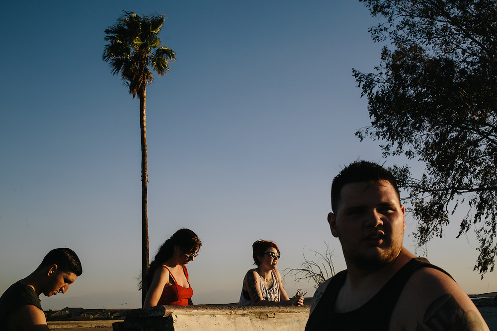 Christopher DeLeon, 20, right, his wife Catherine DeLeon, 19, second from left, and friends watch skaters  at Kern Side, an little known skate park in the foothills outside of Bakersfield, California.