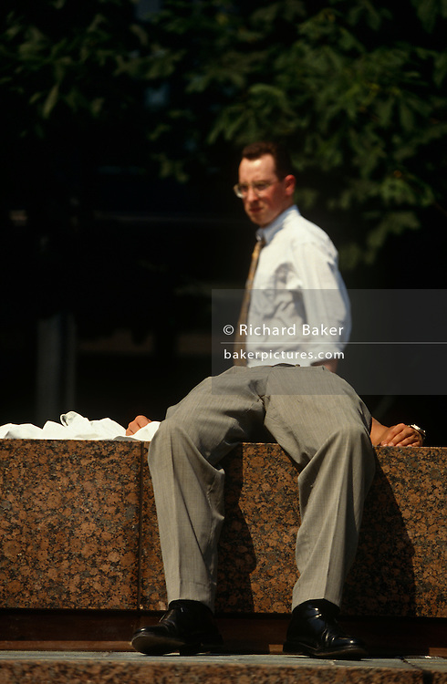 We see the upper-body of a businessman walking past the lower-body of another man also wearing a suit. We see the passer-by in a shirt and tie but only two hands, legs and trousers up to the waist of the sunbather, the rest of his upper-body is obscured by the angle of the lens. It is a witty perspective, leading us to believe that the two men are the same person. It is high-summer and lunchtime in the City of London, England, where workers exit their offices to lap up the welcome sunshine during a rare city heatwave that many take advantage of by lying on steps and benches, while fully-dressed in their work clothes.