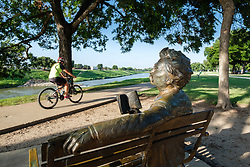 Sculpture of Mark Twain reading book on park bench, with people passing nearby on Trinity Trails path, Fort Worth, Texas, USA.
