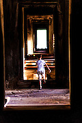 """01 JULY 2013 - ANGKOR WAT, SIEM REAP, SIEM REAP, CAMBODIA:  A tourist's child runs through a hallway in Angkor Wat. Angkor Wat is the largest temple complex in the world. The temple was built by the Khmer King Suryavarman II in the early 12th century in Yasodharapura (present-day Angkor), the capital of the Khmer Empire, as his state temple and eventual mausoleum. Angkor Wat was dedicated to Vishnu. It is the best-preserved temple at the site, and has remained a religious centre since its foundation– first Hindu, then Buddhist. The temple is at the top of the high classical style of Khmer architecture. It is a symbol of Cambodia, appearing on the national flag, and it is the country's prime attraction for visitors. The temple is admired for the architecture, the extensive bas-reliefs, and for the numerous devatas adorning its walls. The modern name, Angkor Wat, means """"Temple City"""" or """"City of Temples"""" in Khmer; Angkor, meaning """"city"""" or """"capital city"""", is a vernacular form of the word nokor, which comes from the Sanskrit word nagara. Wat is the Khmer word for """"temple grounds"""", derived from the Pali word """"vatta."""" Prior to this time the temple was known as Preah Pisnulok, after the posthumous title of its founder. It is also the name of complex of temples, which includes Bayon and Preah Khan, in the vicinity. It is by far the most visited tourist attraction in Cambodia. More than half of all tourists to Cambodia visit Angkor.      PHOTO BY JACK KURTZ"""