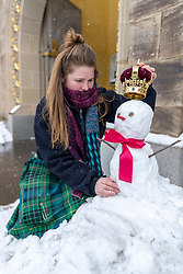 Staff at the Palace of Holyrood House in Edinburgh have made a royal welcome to visitors today by building a snow queen resplendent with a crown on its head.<br /> <br /> Pictured: Elaine Bridge, one of the staff adding the crown to the snow queen outside the place visitor centre.