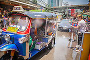 "13 APRIL 2013 - BANGKOK, THAILAND:   Thais and foreign tourists throw water on tourists in a ""tuk-tuk"" (three wheeled taxi) during Songkran celebrations on Soi Nana, off of Sukhumvit Road in Bangkok. Songkran is celebrated in Thailand as the traditional New Year's Day from 13 to 16 April. The date of the festival was originally set by astrological calculation, but it is now fixed. If the days fall on a weekend, the missed days are taken on the weekdays immediately following. Songkran is in the hottest time of the year in Thailand, at the end of the dry season and provides an excuse for people to cool off in friendly water fights that take place throughout the country. Songkran has been a national holiday since 1940, when Thailand moved the first day of the year to January 1.  PHOTO BY JACK KURTZ"