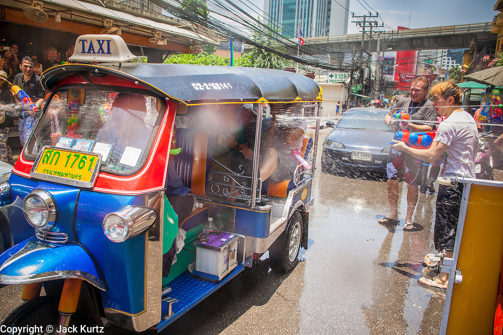 """13 APRIL 2013 - BANGKOK, THAILAND:   Thais and foreign tourists throw water on tourists in a """"tuk-tuk"""" (three wheeled taxi) during Songkran celebrations on Soi Nana, off of Sukhumvit Road in Bangkok. Songkran is celebrated in Thailand as the traditional New Year's Day from 13 to 16 April. The date of the festival was originally set by astrological calculation, but it is now fixed. If the days fall on a weekend, the missed days are taken on the weekdays immediately following. Songkran is in the hottest time of the year in Thailand, at the end of the dry season and provides an excuse for people to cool off in friendly water fights that take place throughout the country. Songkran has been a national holiday since 1940, when Thailand moved the first day of the year to January 1.  PHOTO BY JACK KURTZ"""