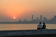 View of mature couple sitting by Marine Drive Promenade, Mumbai, India