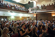 Attendees are clapping hands and cheering during The Sunday Assembly (today held inside Conway Hall in central London), an atheist service founded by British comedians Sanderson Jones and Pippa Evans in 2013, in London, England. The gathering is designed to bring together non-religious people who want a similar communal experience to a religious church. Satellite assemblies have been established in over 30 cities including New York, San Diego, and Dublin.