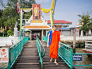 21 NOVEMBER 2012 - BANGKOK, THAILAND:  A Budhist monk passes under a photo of Bhumibol Adulyadej, the King of Thailand, as he boards a ferry to go to Bangkok on the Chao Phraya River. A network of ferries connect the Thonburi section of Bangkok to Bangkok proper, crossing the Chao Phraya River. The fare is 3 Thai Baht, about $ 0.15 (US). The boats are the fastest way to get from north to south in Bangkok. Thousands of people commute to work daily on the Chao Phraya Express Boats and fast boats that ply Khlong Saen Saeb. Boats are used to haul commodities through the city to deep water ports for export.   PHOTO BY JACK KURTZ