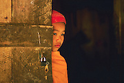 A young novice Theravada Buddhist monk peers from behind a door to the monks quarter of a small rural monastery in Xishuangbanna.