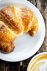 Golden brown croissant on White Plate with Coffee to the side