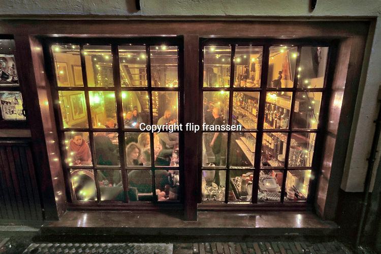 Nederland, Nijmegen, 23-12-2019 Rond de stevenskerk, het Stevenskerkhof, bevinden zich nog wat middeleeuwse historische gebouwen die bespaard zijn gebleven in de oorlog. Hier is o.a. het oudste cafe van de stad, In de Blaauwe, blauwe, hand . Nijmegen claimt de oudste stad van Nederland te zijn . De donkere dagen voor kerst . Mensen zoeken gezelligheid en gezelschap in de horeca .Foto: Flip Franssen
