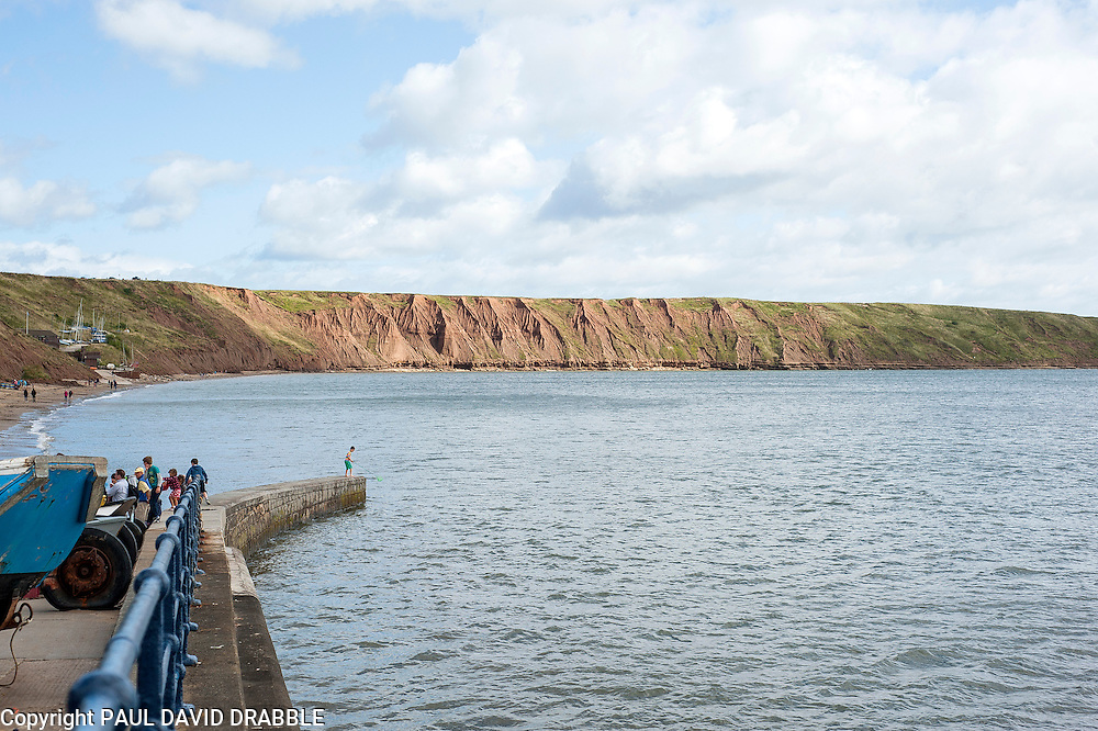 The view, with the tide in, from Coble Landing at Filey North Yorkshire towards the cliffs and Filey Brigg