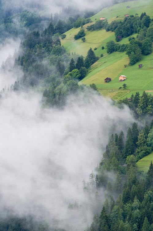 IFTE-NB-007626; Niall Benvie; Cut hay meadows near Fliess; Austria; Europe; Austria; Tirol; clouds mist hut building hay barn fields; vertical; high above steep; green; farmland grassland meadow; 2008; July; summer; mist; agriculture; Wild Wonders of Europe Naturpark Kaunergrat
