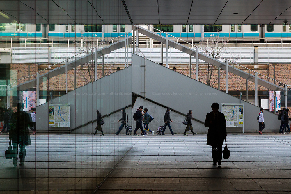 A train and eople reflected in a glass building near Akihabara station,  Akihabara, Tokyo, Japan. Friday January 10th 2020