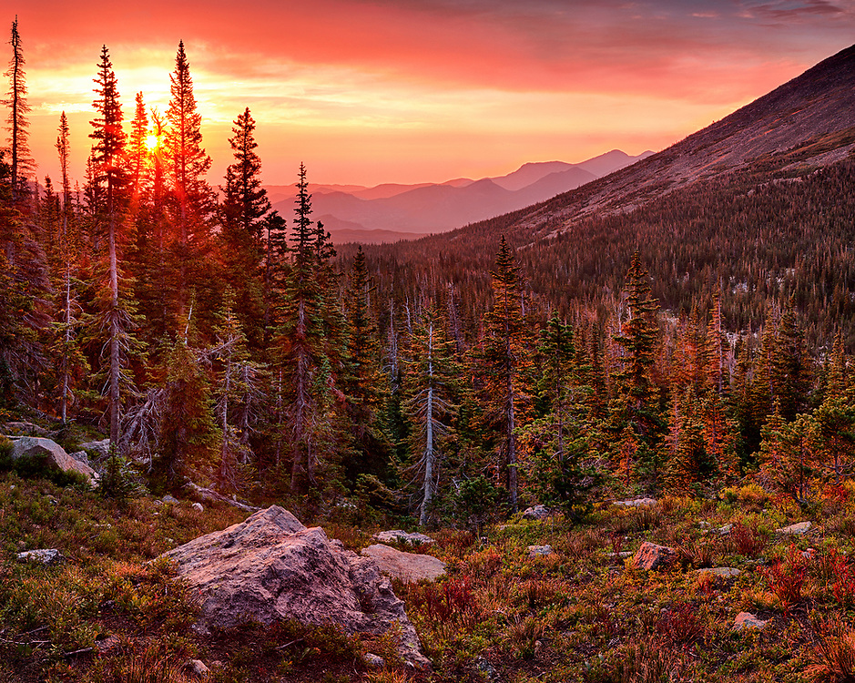 The sun rises above Mill Creek Canyon in Rocky Mountain National Park. Colorful sunrises are not unusual here, but on this morning the colors were enhanced by the smoke from several major wildfires burning in Colorado.
