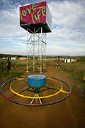 PlayPump near Pretoria, South Africa. The PlayPump Water System uses the energy of children at play to operate a water pump. It is manufactured by the South African company Roundabout Outdoor. It operates in a similar way to a windmill-driven water pump. The PlayPump water system is a like a playground merry-go-round attached to a water pump. The spinning motion pumps underground water into a 2,500-liter tank raised seven meters above ground. The water in the tank is easily dispensed by a tap valve. According to the manufacturer the pump can raise up to 1400 liters of water per hour from a depth of 40 meters. Excess water is diverted below ground again. The storage tank has a four-sided advertising panel. Two sides are used to advertise products, thereby providing money for maintenance of the pump, and the other two sides are devoted to public health messages. There are more than 1000 PlayPump systems in five countries of Sub-Saharan Africa, providing clean drinking water to more than 1 million people in need.