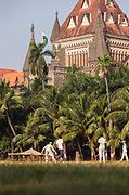 View of people in front of Cricket match in Shivaji Park with Mumbai High Court building behind, India