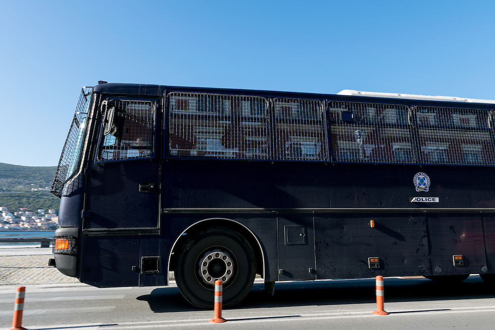 13 April 2016: Reinforced police bus driving by on the small town road on the Greek Island of Samos, where all refugees have been moved to a closed camp, so-called hotspot, where they are kept awaiting registration, identification, and transfer for resettlement in a European country. Many refugees stay for weeks or even several months awaiting resettlement. Refugees and volunteer workers report lack of information, long lines for food, and poor nutrition.