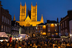 "© Licensed to London News Pictures. 7/12/2013. Lincoln, UK. Lincoln City Centre was packed with Christmas shoppers this weekend. Pictured, The floodlit Lincoln Cathedral stands proud as the Christmas market shoppers throng in the market square below. Thousands of shoppers filled the City Centre and stewards were called in to direct people up the narrow ""Steep Hill"" towards the upper area of Lincoln near the Cathedral. The Christmas Market now in it's 31st year with over 250 stalls attracts people from abroad as well as UK visitors. Photo credit : Dave Warren/LNP"