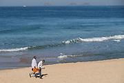 Musicians walk along Ipanema beach early morning in Rio de Janeiro, Brazil.