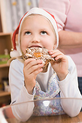 Girl eating gingerbread, looking up