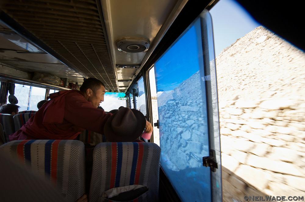 A Tibetan monk throws prayers out a bus window as it crosses a high mountain pass near Dege, Tibet.