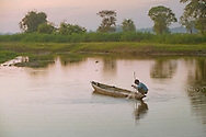 A fisherman pulls his net out of the water, Majuli Island, Assam, India.