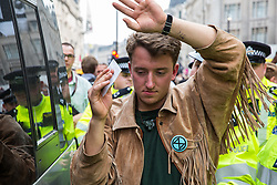 London, UK. 17th April 2019. Police officers arrest a climate change activist from Extinction Rebellion as protesters continue to occupy Oxford Circus, creating a carnival-like atmosphere in the heart of London's shopping district around a sound system on the Ship of Truth.