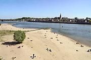 """Nederland, Nijmegen, 26-4-2020  Tijdens dit warme weekend was het voor veel mensen moeilijk thuis te blijven . Beeld van het waalstrandje op Veur-Lent. Bezoekers hebben met stenen """" 1,5 M """" in het zand gelegd wat goed zichtbaar is vanaf de fietsbrug. Waal, rivier,rivierengebied,stevenskerk,skyline,stadsgezicht .Foto: Flip Franssen"""