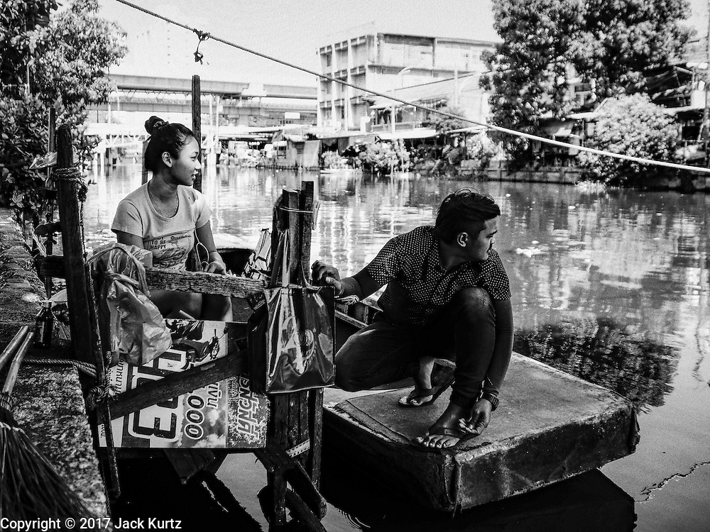 16 FEBRUARY 2017 - THEPHARAK, SAMUT PRAKAN, THAILAND: A boatman who uses his small boat as a ferry, and his girlfriend, wait for passengers on Khlong Samrung, in the Bangkok suburbs. The boatman pulls it across using a system of ropes and pulleys. He's been working on the boat since he was a child. Small ferries like this used to be common in Bangkok but many of the khlongs (the canals that used to crisscross Bangkok) have been filled in and bridges have been across the remaining khlongs. Now there are only a handful of the ferries left. This ferry charges 2 Baht (the equivalent of about .06¢ US) per person to take a person across the khlong.      PHOTO BY JACK KURTZ