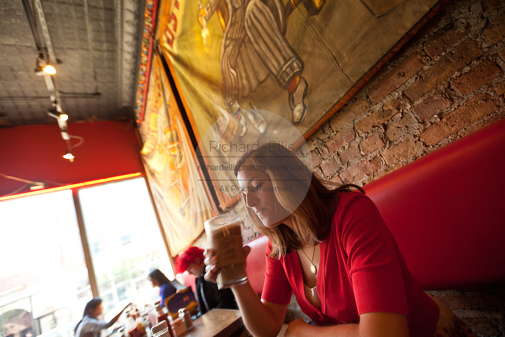 A young lady drinks a latte at a trendy cafe in the hip neighborhood of Wicker Park in Chicago, IL, USA.