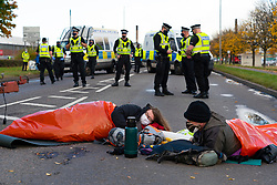 Grangemouth, Scotland, UK. 23 October 2020. Extinction Rebellion climate change protesters block entrance to INEOS headquarters at Grangemouth. Protesters have locked themselves together with chain and have parked a yacht in the road blocking access. Police have closed Inchyra Road. Iain Masterton/Alamy Live News
