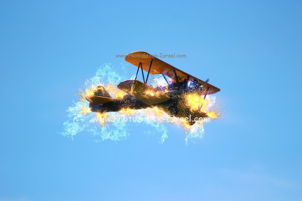 Digitally enhanced side view image of a burning biplane in flight