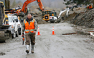 A rescue worker carrying a saw leaves the mudslide after searching for victims in Oso, Washington March 30, 2014. Local churches offered prayers on Sunday for the victims of last week's devastating mudslide in Washington state and words of solace for grieving families and friends, many of whom are still waiting for news of missing loved ones.  REUTERS/Rick Wilking (UNITED STATES)