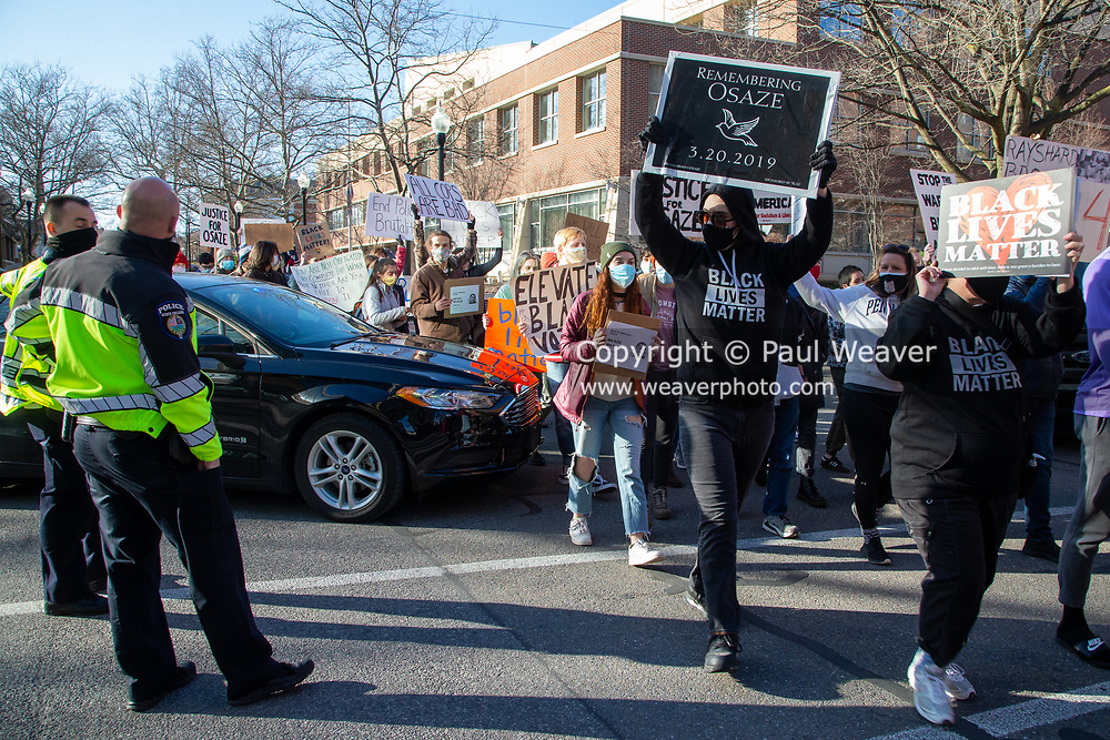 People protesting the police killing of Osaze Osagie march past State College police officers.