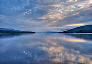 Lake George, Adirondacks, NY.  A wall of overcast greeted me on this morning at the southern end of Lake George, and I didn't hold out a lot of hope for sunrise.  But the fabric of gray began to tear a little here and there, the light used the opportunity to highlight and color the sky, and the dark water threw back the reflection.  I am headed north, into the heavier fog laying over Dunham Bay, but here I wait to see how the morning reveals itself.  What kind of mood are you in, I wonder.  You are unsure, but there is a sunrise anyways.  And for now I hope the morning smiles on me.
