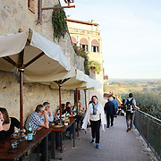 SAN GIMIGNANO, ITALY - OCTOBER 25: A cafe scene overlooking the countryside in San Gimignano, Italy.  San Gimignano is an Italian hill town in Tuscany, southwest of Florence. Encircled by 13th-century walls, its old town centers on Piazza della Cisterna, a triangular square lined with medieval houses. It has a skyline of medieval towers, including the stone Torre Grossa. San Gimignano, Tuscany, Italy. 25th October 2017. Photo by Tim Clayton/Corbis via Getty Images)
