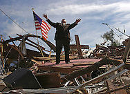 From a mound of rubble, Lady Lake Church of God pastor Larry Lynn leads his congregation and many visitors in prayer during an outdoor Sunday service February 04, 2007.  An early morning tornado destroyed the church on February 02, 2007.