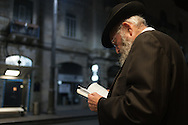 An Orthodox Jewish man reads his prayer book as he waits for a train in Jerusalem